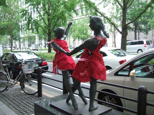野外彫刻に赤いドレス