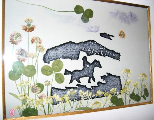 押花絵ア-ト 3 中央の馬に乗った人物とその上下は、チエコさんの父親が残した版画を活用して自然の花と三つ葉を添えたもの。戦前の移住者であった父への手向けか。