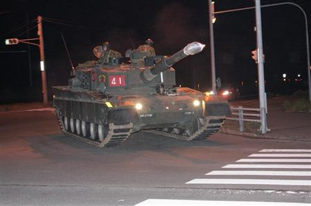 :::市街地の交差点で左折の方向指示器を点滅させる90式戦車