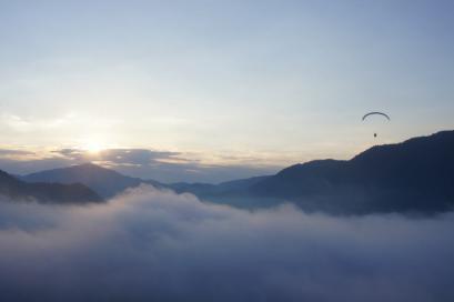 朝日が昇る雲海をモーターパラグライダーが優雅に飛んでいました。