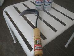 [写真]草刈り用の鎌とミニ缶サイダー