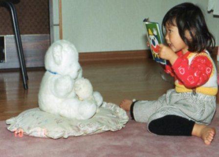 くまさんに絵本の読み聞かせをするあーちゃん(2歳)