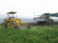 [写真]ベアハウスの隣の畑を整地するブルドーザー2台
