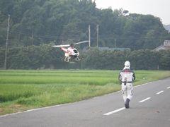 [写真]農薬散布用のラジコンヘリを操縦している様子